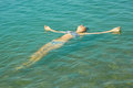 Teen girl lying on the sea water surface turquoise in shallow coastal area Royalty Free Stock Images