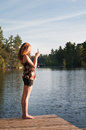 Teen girl photographing with her phone using to take a photograph of a lake Royalty Free Stock Image