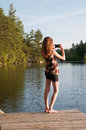Teen girl photographing with her phone using to take a photograph of a lake Royalty Free Stock Photo