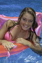 Teen girl in pink bikini on a float Royalty Free Stock Image