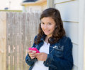 Teen girl playing music with smartphone earings Royalty Free Stock Photo