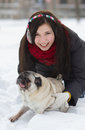 Teen girl with pug puppy in snow Stock Image