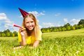 Teen girl ready for birthday party portrait of little with noisemaker horn and cap laying outside with happy expression on sunny Royalty Free Stock Images
