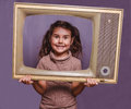Teen girl retro child framed television frame smiling on gray ba background Stock Photos