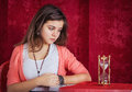 Teen girl with sandglass pretty sad looking at on the table concept time slipping away tedious waiting Royalty Free Stock Photos