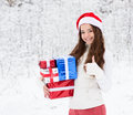 Teen girl with santa hat and red gift boxes showing thumbs up in winter forest