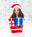 Teen girl with santa hat and red gift boxes standing in winter forest