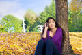 Teen girl sitting against autumn tree using cell phone Royalty Free Stock Photo