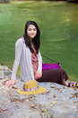 Teen girl sitting by river in thailand biracial next to smiling Royalty Free Stock Image