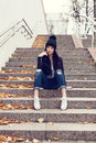 Teen girl sitting on stairs against grunge wall portrait of a beautiful woman hipster outdoors lifestyle Stock Photo