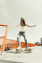 Teen girl skater riding skateboard on street.