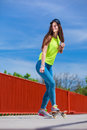 Teen girl skater riding skateboard on street. Royalty Free Stock Photo