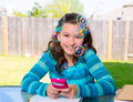 Teen girl with smartphone doing homework american latin on backyard Royalty Free Stock Photography