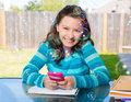 Teen girl with smartphone doing homework american latin on backyard Royalty Free Stock Image