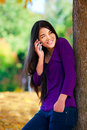 Teen girl standing against autumn tree talking on cell phone Royalty Free Stock Photo