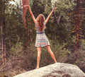 Teen girl standing on large rock with open arms a in a sundress her back to the camera holds up her to the sky while top of a in a Royalty Free Stock Photography
