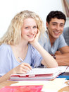 Teen girl studying in the library with her friends Royalty Free Stock Photos