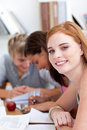 Teen girl studying in the library with her friends Royalty Free Stock Photo