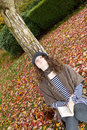 Teen girl thinking while outside in the autumn season vertical photo of teenage looking upward lying against a tree during dressed Royalty Free Stock Photography