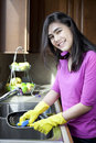 image photo : Teen girl washing dishes at kitchen sink