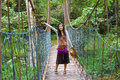 Teen girl on wooden hanging bridge in woods biracial waving arm Royalty Free Stock Image