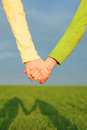 Teen girls holding hands against blue sky Stock Photo