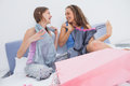 Teen girls sitting on bed after shopping and holding new clothes Royalty Free Stock Photography