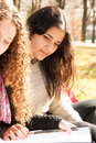 Teen girls studying outdoors in a sunny day Stock Photography