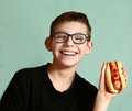 Teen handsome boy in myopia glasses with hot dog Royalty Free Stock Photo