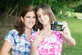 Teen and her young mother taking a self picture hispanic teenager at beautiful park Stock Image