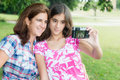Teen and her young mother taking a self picture hispanic teenager at beautiful park Royalty Free Stock Photos