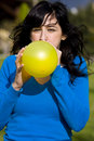 Teen inflating yellow balloon Royalty Free Stock Photography