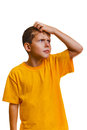 Teen kid boy blonde in yellow shirt scratching his head looking up thinking isolated Royalty Free Stock Photos