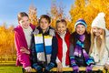 Teen kids in autumn park five happy school age boy and girls smiling and standing together with large happy smiles and stylish Stock Photo