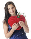 Teen with loving pillow an attractive young in formal wear happily holding a red heart shaped a pocket full of white rose buds on Royalty Free Stock Photo