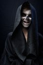 Teen with make up of skull in black cloak laughs the a Royalty Free Stock Photo