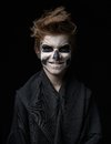 Teen with make up of skull in black cloak laughs the a Stock Photography