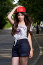 Teen model beautiful long haired on pave red cap grey t shirt dark blue shorts Royalty Free Stock Photo