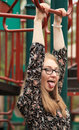 Teen at park teenage girl the hanging on the monkey bars with her tongue sticking out being silly Stock Image