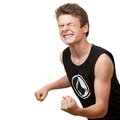 Teen pulling a fist with eyes closed winning attitude and isolated on white background Stock Photos