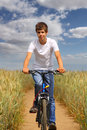 Teen riding a bicycle through wheat field Royalty Free Stock Photography