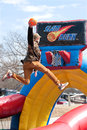 stock image of  Teen Soars Above Rim To Dunk Basketball In Carnival Game