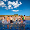 Teen surfers group running beach splashing boys and girls happy to the water Stock Photography