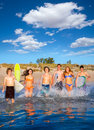 Teen surfers group running beach splashing boys and girls happy to the water Royalty Free Stock Images