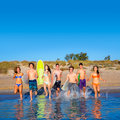 Teen surfers group running beach splashing boys and girls happy to the water Stock Image