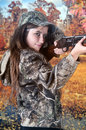 Teen taking aim a pretty young looking at the viewer as she prepares to take with her rifle she s standing near autumn wetlands Stock Photos