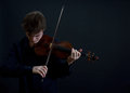 Teen violinist virtuoso male on dark background bowed Stock Photos