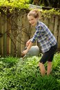 Teen watering flowers Royalty Free Stock Photo
