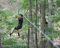 Teen zipline boy ziplining in the woods Royalty Free Stock Photos