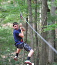 Teen ziplining boy in the woods Stock Photography